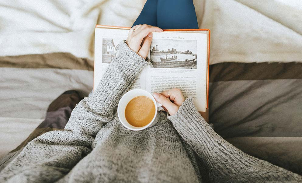 An image of a person reading and drinking coffee.