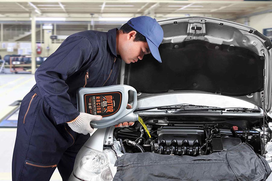 An image of a technician adding oil to a car.