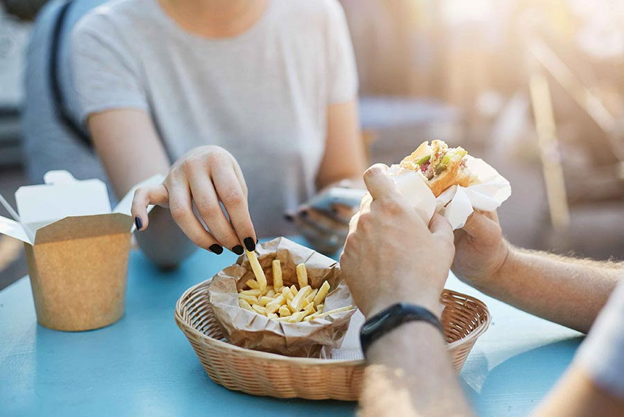 Man and woman eating fries and a burger in paper containers