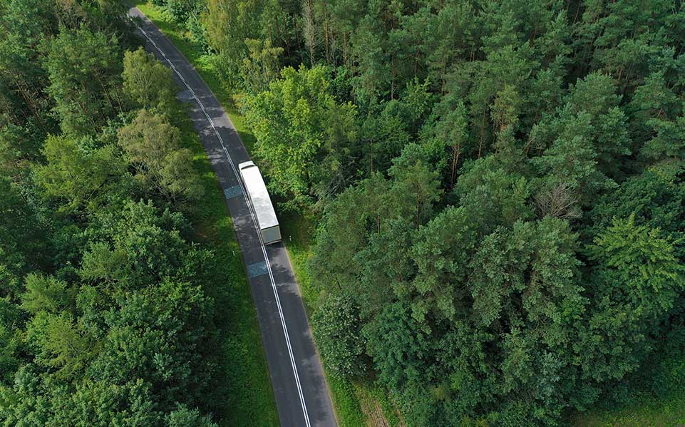 A tractor trailer driving down a forest highway.