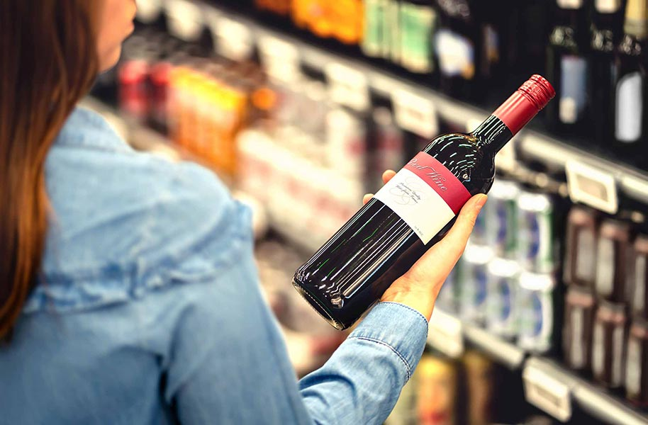 An image of a woman looking at a wine label.