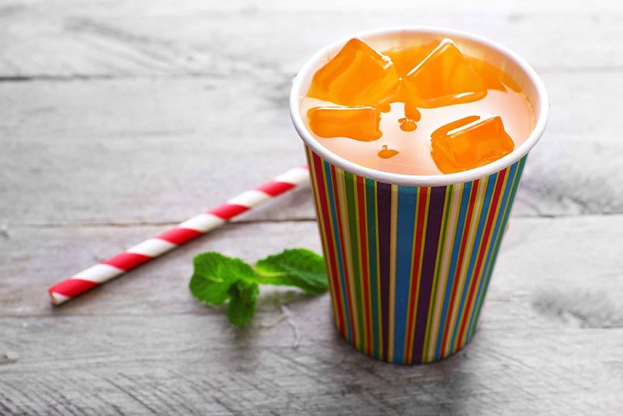 An image of punch in a paper cup sitting next to a paper straw.