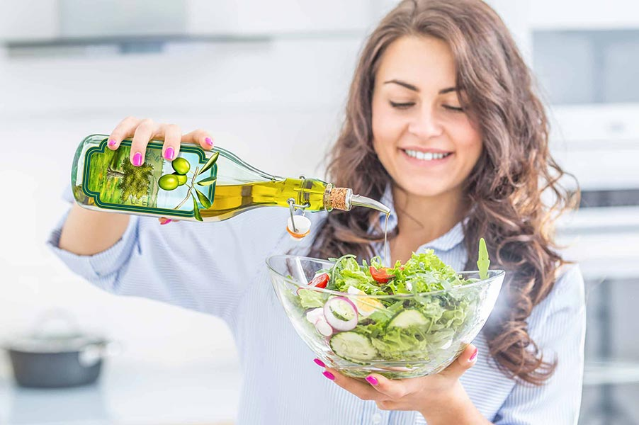 An image of a woman with a salad and a bottle of olive oil.