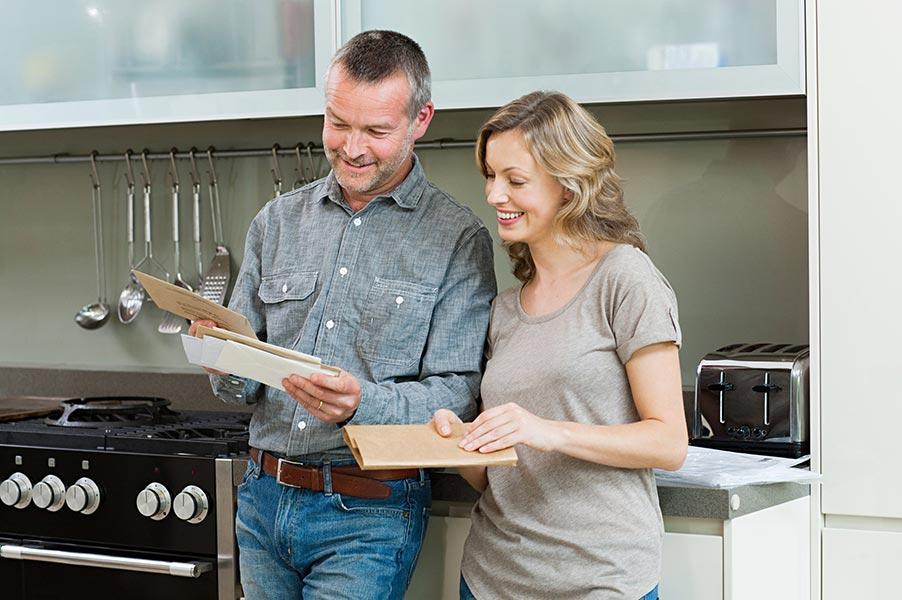 couple holding mail envelopes