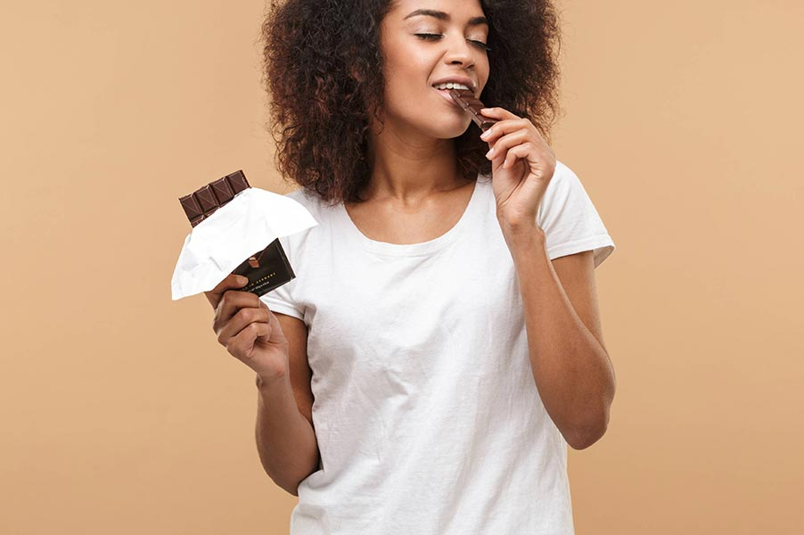 An image of a woman eating a chocolate bar.