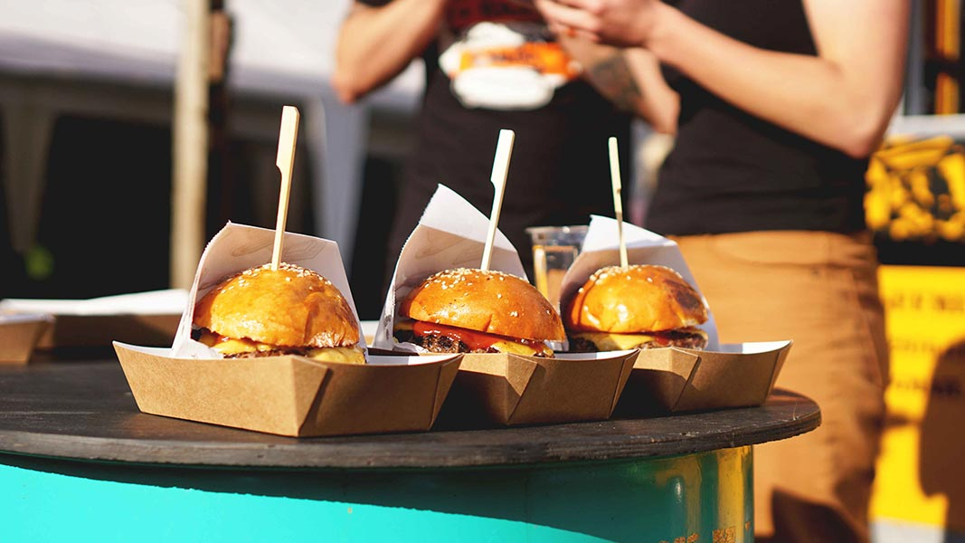 Cheeseburgers in paper trays on a table.