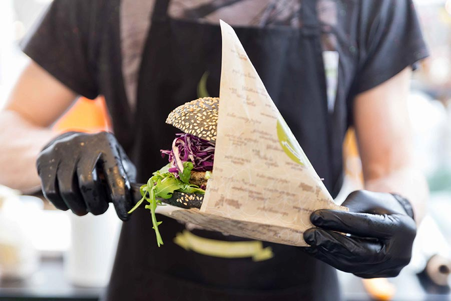 An image of restaurant server carrying a wrapped sandwich.