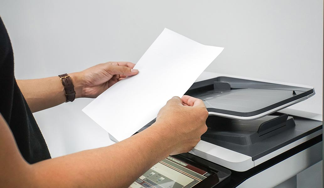 An image of a person holding paper next to a copier.