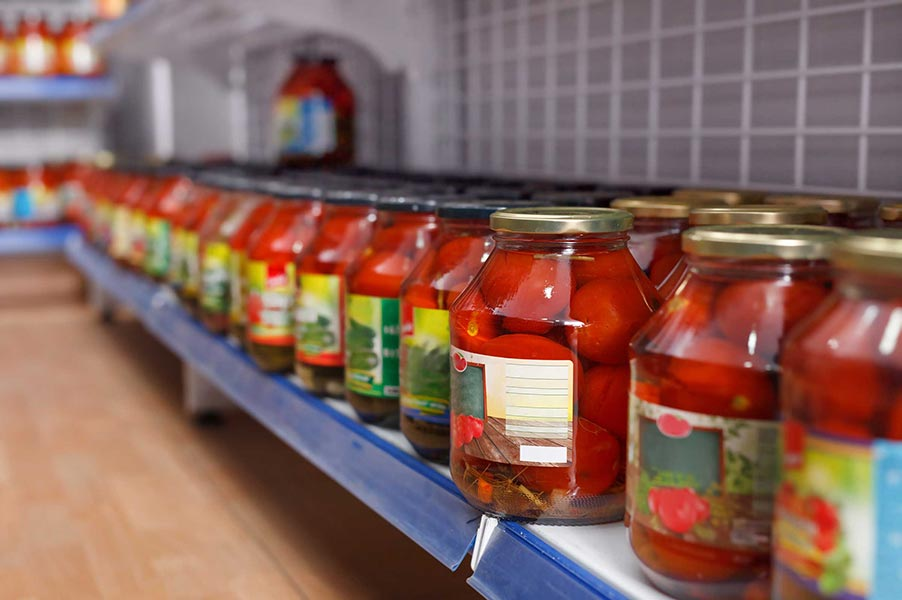 A row of jarred tomatoes on a store shelf