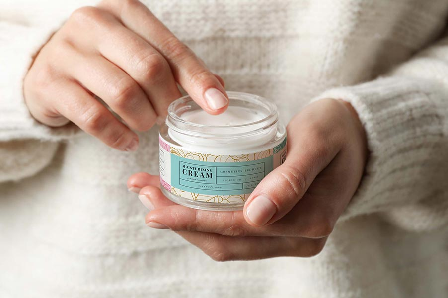 An image of someone holding a jar of hand cream.