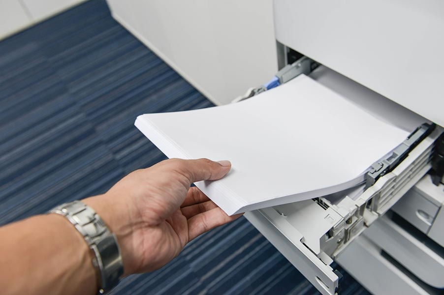 Office paper being loaded into a printer