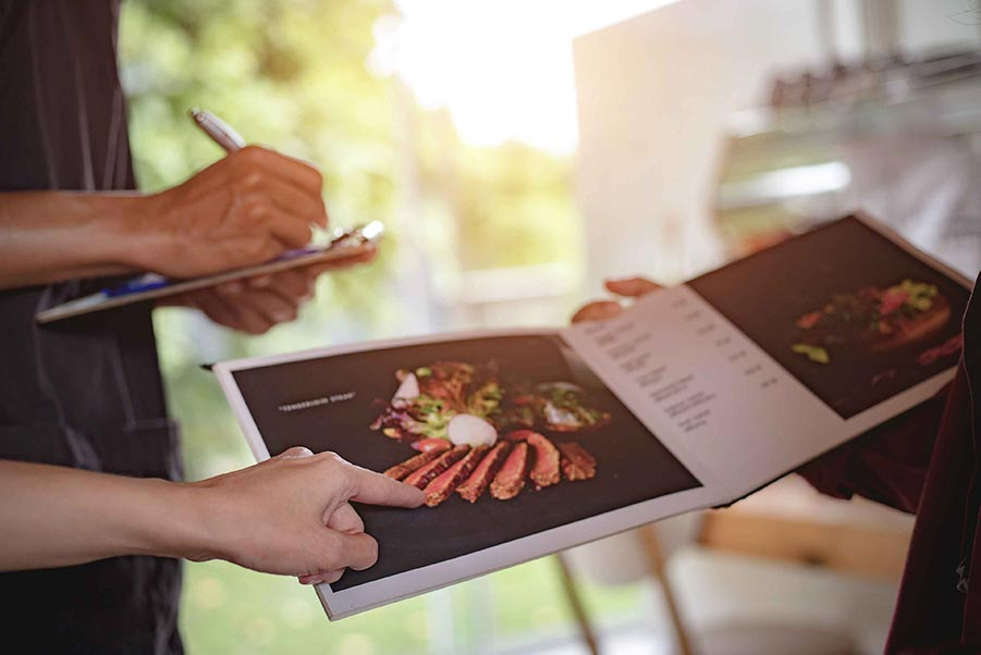 An image of a person pointing to a colorful food menu.
