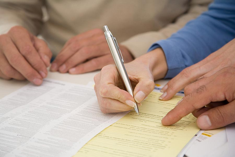 An image of people filling out documents.
