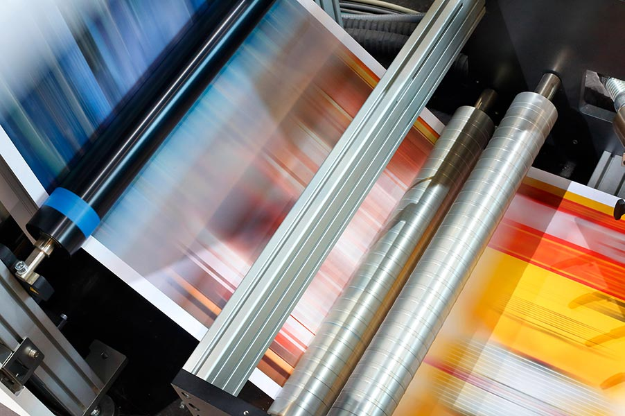 An image of paper running through a printing press.