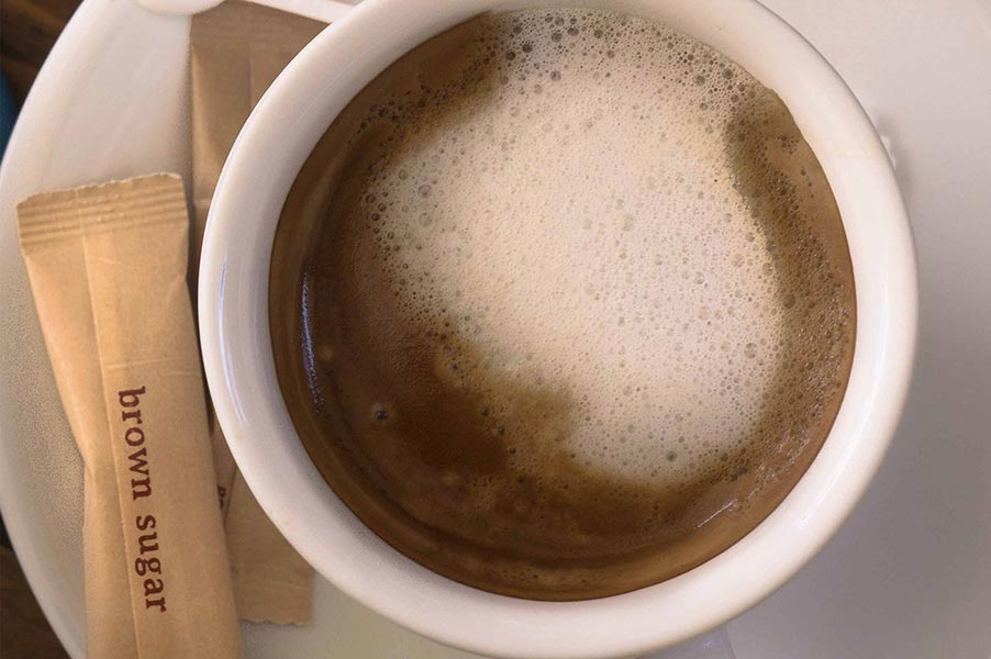 An image of a cup of coffee and sugar packets.