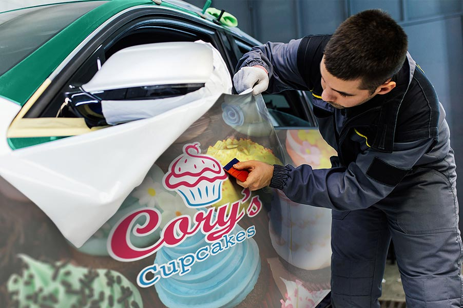 Image of a man applying a vinyl decal to a car.