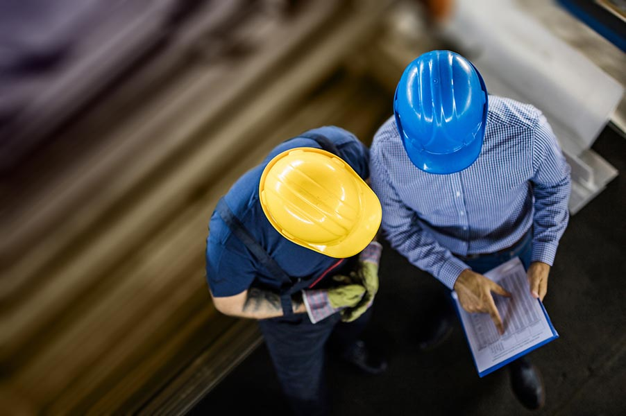 two employees in hardhats looking at a clipboard