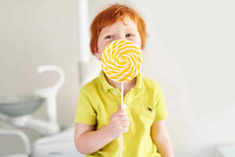 In image of a young boy eating a lollipop.