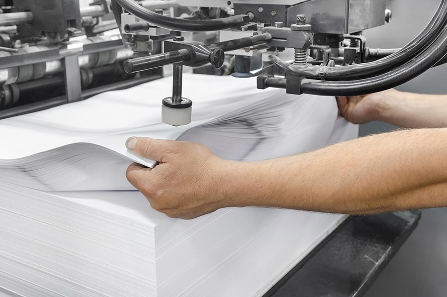 Large stack of paper being pressed