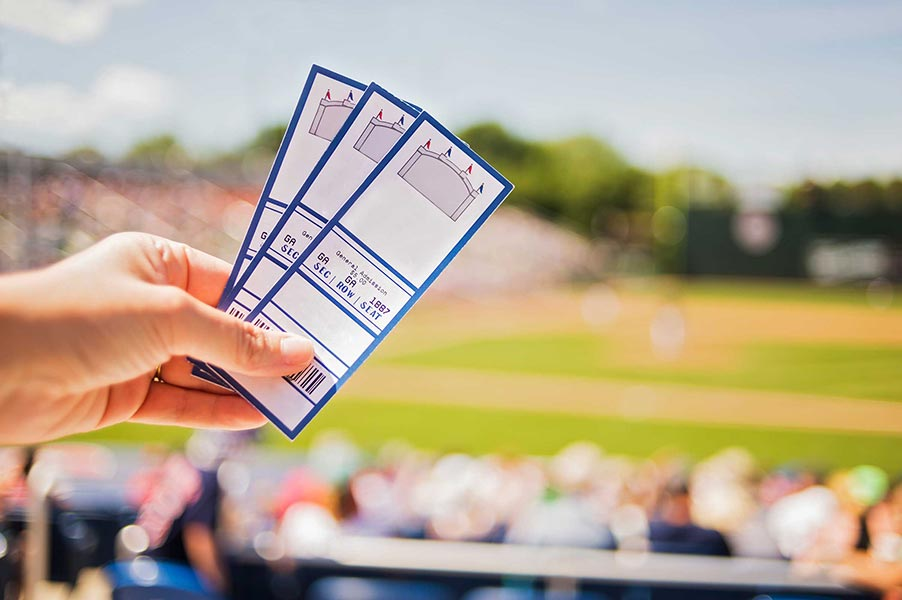 A hand holding tickets with a baseball field in the background.