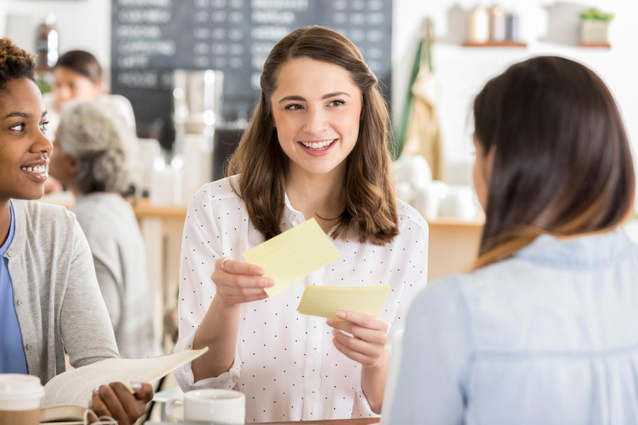 Woman holding note cards with 2 other women.